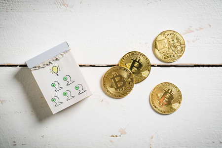 bitcoins with tear-off calendar with idea symbol on wooden background