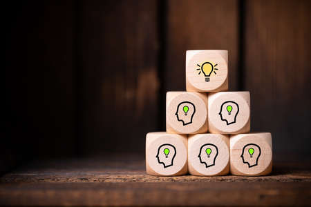 Foto de many people together having an idea symbolized by icons on cubes on wooden background - Imagen libre de derechos