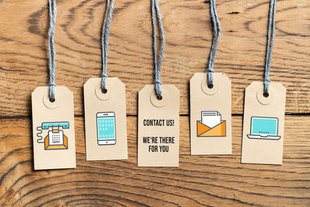 Foto de Hangtags on wooden background with message contact us, we are there for you on wooden background - Imagen libre de derechos