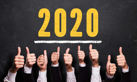 Photo pour many thumbs up in front of blackboard with message 2020 - image libre de droit