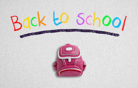 Photo pour message back to school and a backpack piece on paper background - image libre de droit