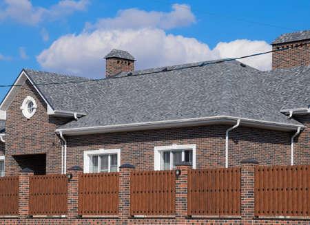 Photo pour Asphalt shingle. Decorative bitumen shingles on the roof of a brick house. Fence made of corrugated metal - image libre de droit
