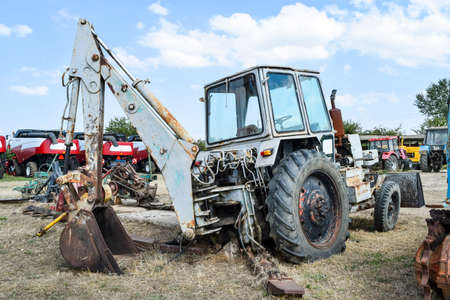 Russia, Temryuk - 15 July 2015: Tractor. Bulldozer and grader. Tractor with a bucket for digging soil. The picture was taken at a parking lot of tractors in a rural garage on the outskirts of Temryuk.