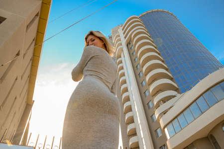 Foto de A girl with a beautiful figure in a gray dress near a tall building - Imagen libre de derechos