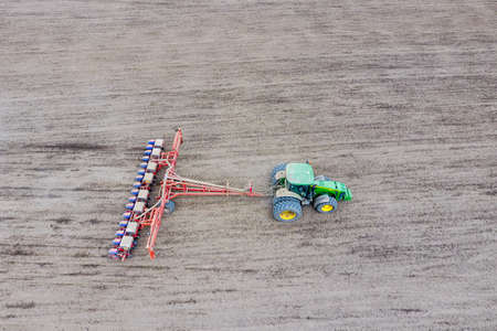 Photo pour Sowing of corn. Tractor with a seeder on the field. Using a seeder for planting corn - image libre de droit