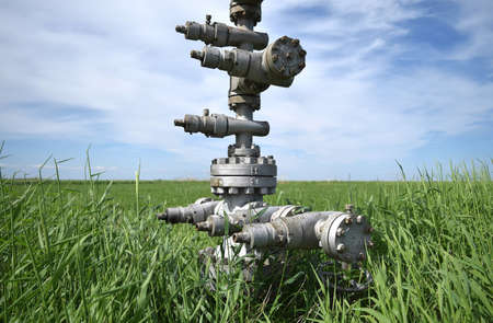 Photo pour Canned oil well against the sky and field. Equipment of an oil well. Shutoff valves and service equipment. - image libre de droit