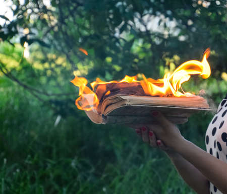 Burning book in the hands. Burning books in the forest. The girl holds a burning book in her hands. A young woman in a forest burns a book.