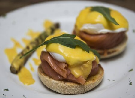 Delicious eggs benedict with smoked salmon and hollandaise sauce served on wholegrain bun bread