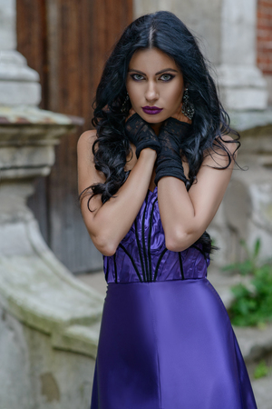 Beautiful young witch in lilac silk dress