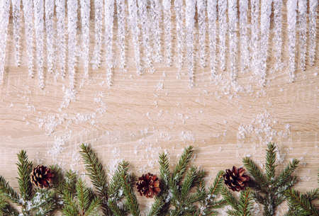 Photo pour Above view of winter Christmas banner. At the top are plastic icicles and at the bottom are fir tree branches with pine cones. Snow scattered, wood board background. - image libre de droit