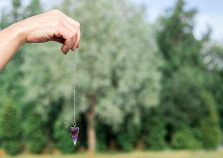 Photo pour Woman hand holding and using purple Amethyst quartz crystal pendulum and using it, white background. - image libre de droit