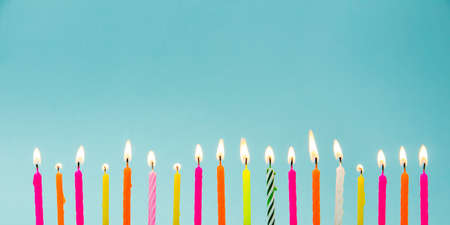 Photo pour Set of many different color shape and pattern birthday candles burning isolated on blue. Happy Birthday card design concept.  Bottom lower border edge a lot of copy space. - image libre de droit
