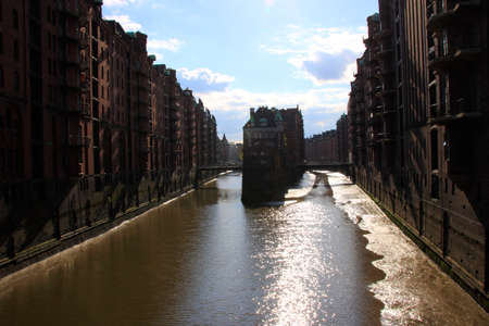 Look into the Speicherstadt in Hamburg. The evening sun is reflected in the lake.
