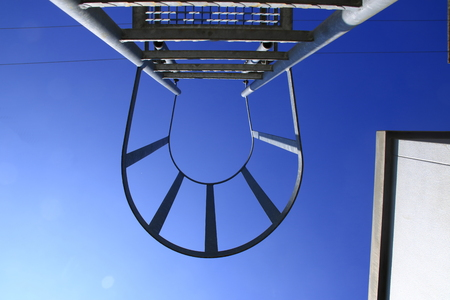 View from below of a ladder with safety bar. The look Symbolizes the ascent with certainty.