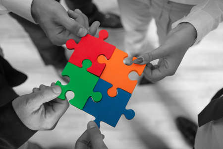 Photo pour Group of business people assembling jigsaw puzzle and represent team support and help concept in office. - image libre de droit