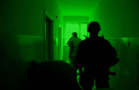 Military training ground ( batlle camp ) in Poland. Soldiers during night exercises - conducting the attack inside the building at night. View through the night vision device.