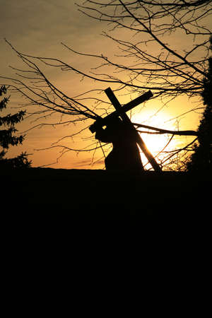 Figure of the Jesus carrying the cross. View of the silhouette at sunset . Empty space for text.