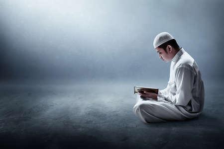 Photo pour Religious muslim man reading holy quran - image libre de droit