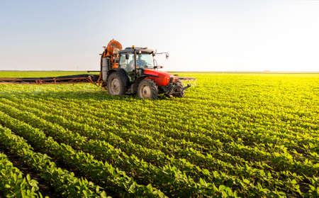 Photo pour Tractor spraying pesticides on soy field  with sprayer at spring - image libre de droit