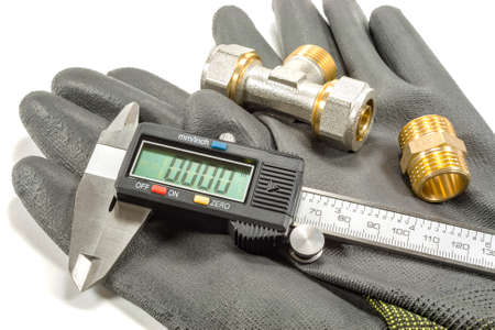 Digital caliper with plumbing fittings and working gloves on a white background