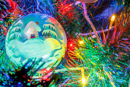 Photo pour Big christmas ball on the branches of decorative fir in the light of colorful lights of electric garland close-up - image libre de droit