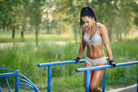 beautiful fitness woman doing exercise on parallel bars sunny outdoor. Sporty girl doing push ups on bars outdoor