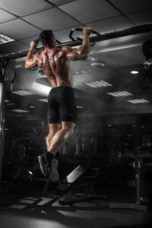 Foto de Muscle athlete man in gym making elevations. Bodybuilder training in gym - Imagen libre de derechos