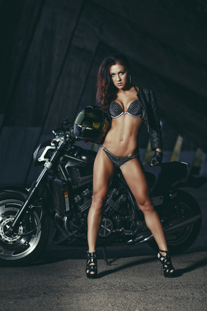 Photo pour Sexy biker fitness girl with perfect slim body on black motorbike in leather wear posing in industrial place - image libre de droit
