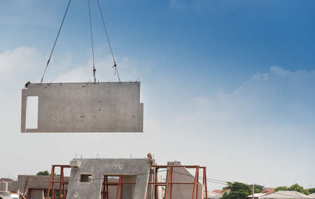 Foto de Construction site crane is lifting a precast concrete wall panel to installation building. - Imagen libre de derechos