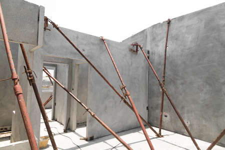 Installation of prefabricated building wall panels supported with u jack. Isolated on white background.
