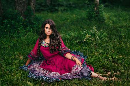 Portrait of a beautiful girl gypsy in violet dress