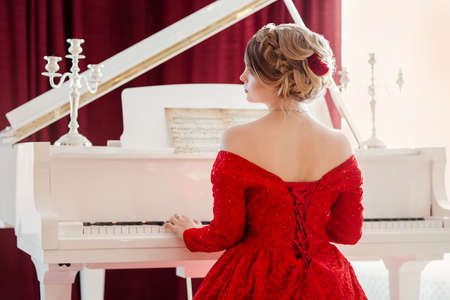 Photo pour A young beautiful woman in a red evening dress sits at the grand piano - image libre de droit