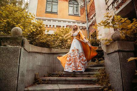 Photo pour Beautiful blond woman in medieval dress walking near old building - image libre de droit