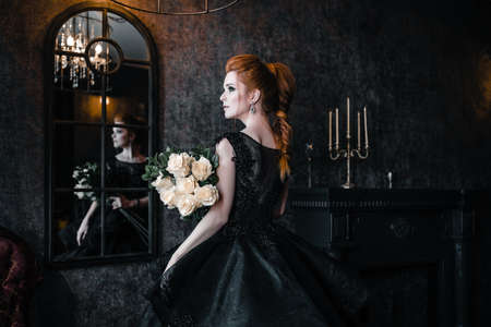 Photo for Attractive woman in black dress in medieval interior - Royalty Free Image