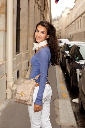 Pretty young woman strolling along a Paris sidewalk