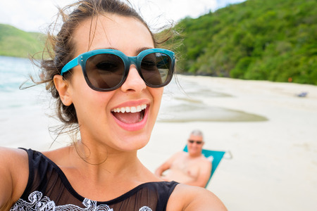 Beautiful young multicultural woman taking a selfie on a Caribbean beach.