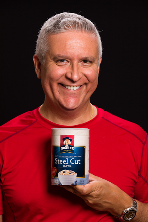 MIAMI, FLORIDA USA - FEBRUARY 4, 2014: Photo of a handsome middle age man holding a container of Quaker Steel Cut Oats used to promote lower cholesterol.