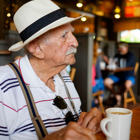Elderly eighty plus year old man wearing a hat in a restaurant setting.の写真素材