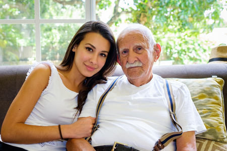 Photo pour Elderly eighty plus year old man with granddaughter in a home setting. - image libre de droit