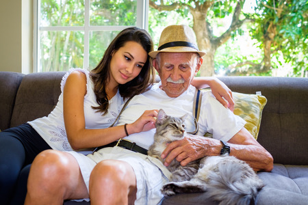 Elderly eighty plus year old man with granddaughter and cat in a home setting.