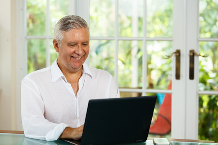 Handsome middle age man portrait in a home setting with a laptop computer.