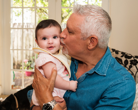 Foto de Grandfather with beautiful five month old baby granddaughter portrait in a home setting. - Imagen libre de derechos