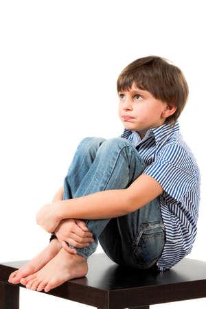 Photo pour boy sitting on a table and thinking - image libre de droit