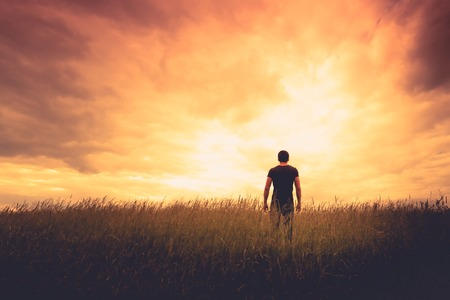 silhouette of man standing in a field at sunset