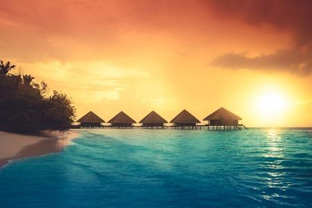 Foto de Over water bungalows with steps into amazing green lagoon - Imagen libre de derechos