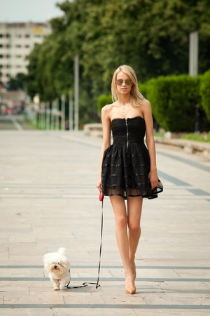 young fashion woman, walking her dog in the park