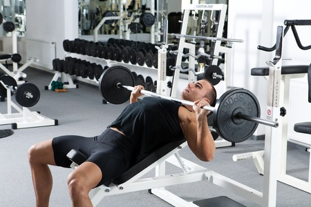 young bodybuilder training in the gym: chest - barbell incline bench press - wide grip