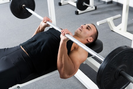 young bodybuilder training in the gym: triceps - close grip barbell bench press