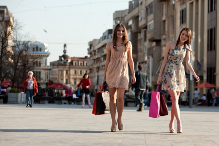 two young women with shopping bags walking in the cityの写真素材
