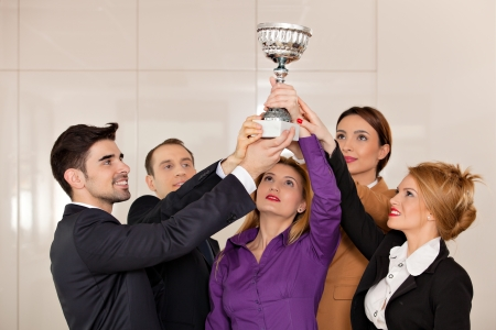 young team holding a trophy; happy business people celebrating their victory